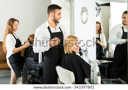 Male hairdresser is making a haircut for a woman in a haird stylying salon. Focus on client - stock photo