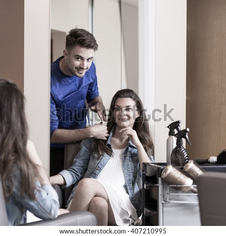 Male hairstylist and female customer in the salon - stock photo