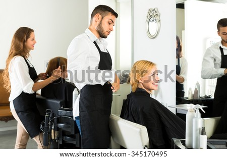 Male hairstylist is making a haircut for a happy woman in a barbershop. Focus on client - stock photo