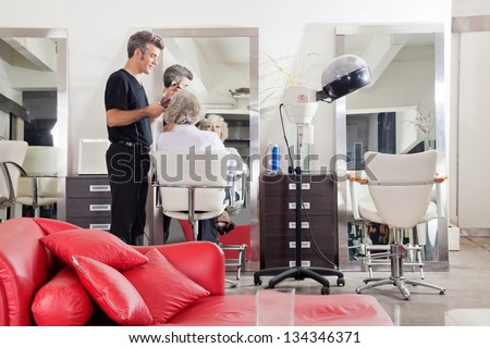 Male hairstylist straightening client's hair at beauty salon - stock photo