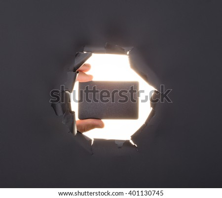 Male hand breaking through the gray paper background and holding key in red box