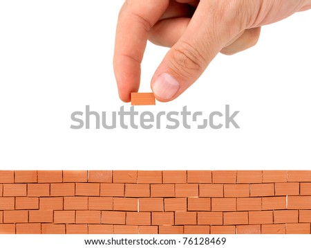 Male hand building a brick wall on white background
