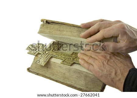 Male hand closed the vintage bible with cross on it isolated over white background - stock photo
