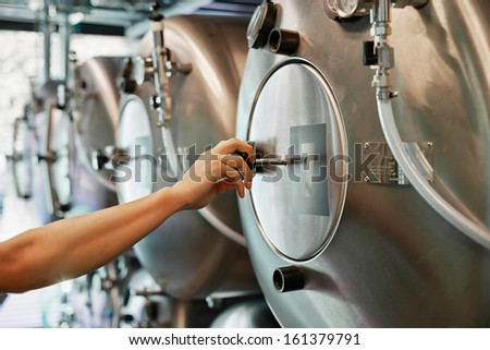 Male hand closes hatch of brewery tank - stock photo