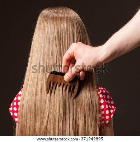 Male hand combing beautiful long hair, closeup shot - stock photo