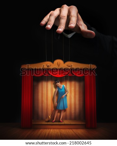 Male hand controlling a small woman puppet - stock photo