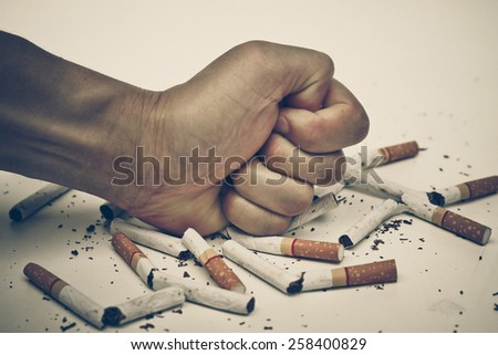 male hand destroying cigarettes - stop smoking concept - stock photo