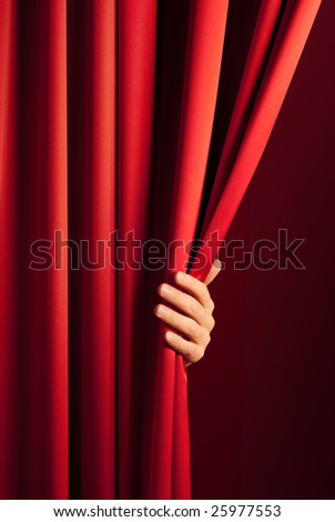male hand disclose the scene shifting the red curtain - stock photo