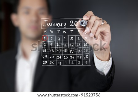 Male hand drawing a calendar - stock photo