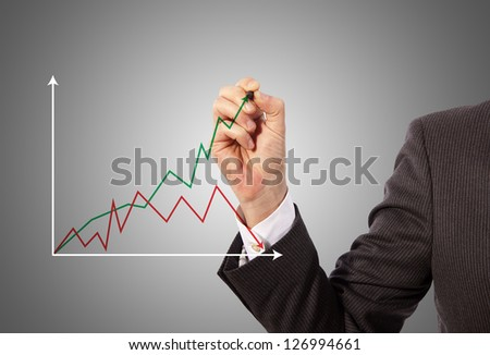 Male hand drawing a graph, grey background - stock photo