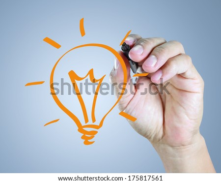 Male hand drawing light bulb - stock photo