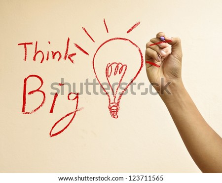 Male hand drawing light bulb and Think big - stock photo