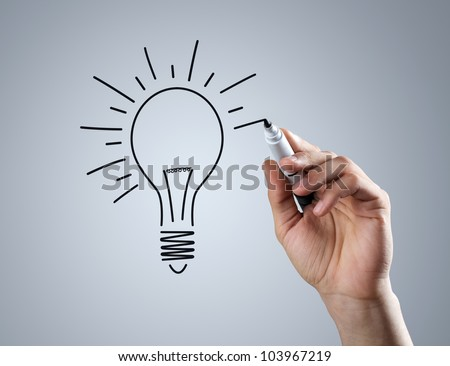 Male hand drawing light bulb over dark background - stock photo