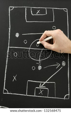 Male hand draws a football play on a chalkboard with chalk. Top view. - stock photo
