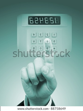 male hand entering safe or door code - stock photo