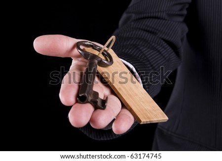 Male hand giving you an old key - stock photo