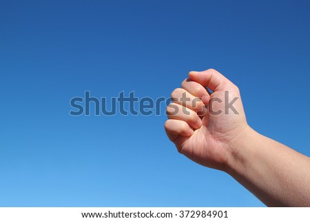 male hand grip gesture in the blue sky - stock photo