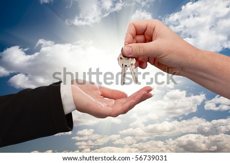 Male Hand Handing Over Keys to Female Hand On Dramatic Clouds and Sun Rays. - stock photo