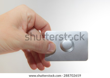 Male hand hold one medical pill in blister pack against white background