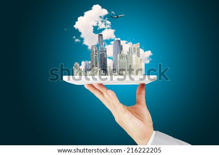 Male Hand Hold tablet with Moderncity Building, Cloud and Airplane - stock photo