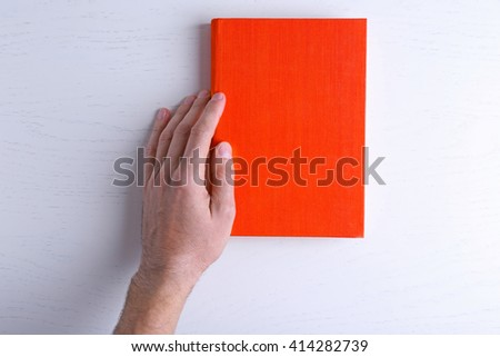 Male hand hold the red  book on white table. - stock photo