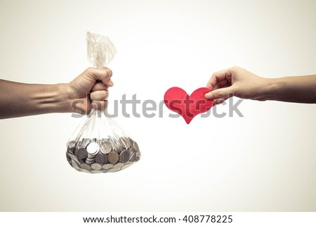 Male hand holding a bag full of coins trying to buy a red hearts from female hand - Buying love concept - stock photo
