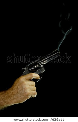 Male hand holding a .38 calibre revolver, with bluish smoke coming out of it. Black Background.