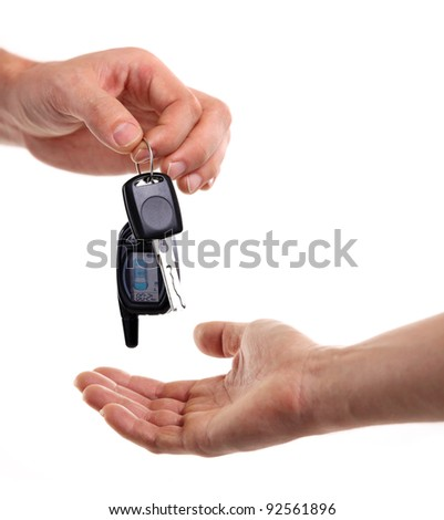Male hand holding a car key and handing it over to another person. - stock photo