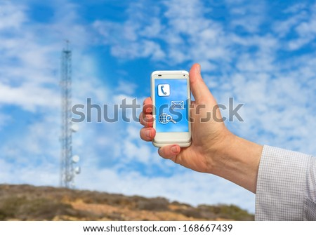 Male hand holding a cellphone in the air. Communication tower and blue sky with clouds background. Rural area. Wireless connection to the internet anywhere concept. Icons on phone. Horizontal view. - stock photo
