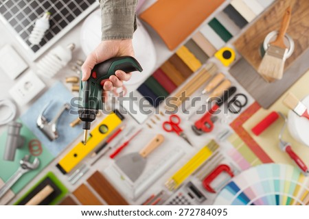 Male hand holding a drill, build and renovation tools on background top view, DIY and improvement concept - stock photo