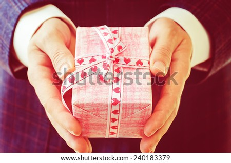 male hand holding a gift. Valentine's day. tinting in retro vintage style. selective focus