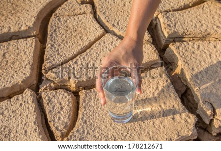 Male hand holding a glass of water over parched soil during drought and dry season - stock photo