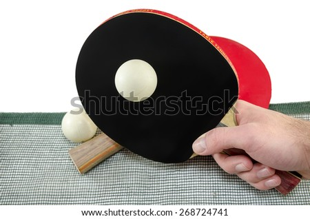 Male hand holding a ping pong racket and a table tennis ball above a net, isolated on white - stock photo
