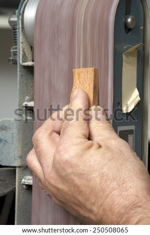 Male hand holding a small piece of cut wood to a table mounted belt sander to smooth the edges on a wood working project. Saw dust everywhere. - stock photo
