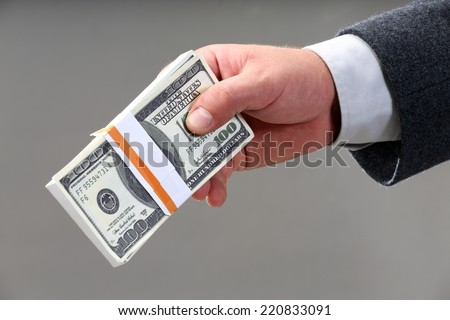 male hand holding a wad of hundred dollar bills - stock photo
