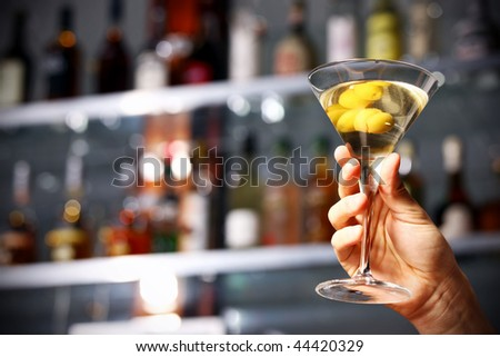 male hand holding alcohol drink with olives