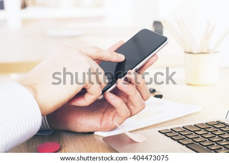 Male hand holding and pointing at smartphone screen in office