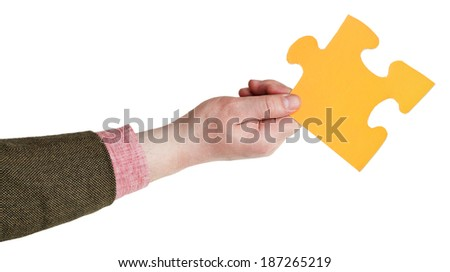 male hand holding big yellow paper puzzle piece isolated on white background