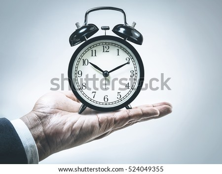 Male hand holding black alarm clock/Business time concept ideas