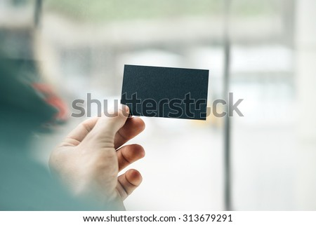 Male hand holding black business card on the window background - stock photo