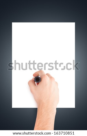 Male hand holding black pen for writing or sketching to blank, white board, paper on dark background. - stock photo