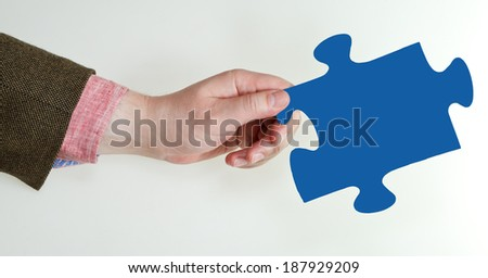 male hand holding blue puzzle piece on grey background