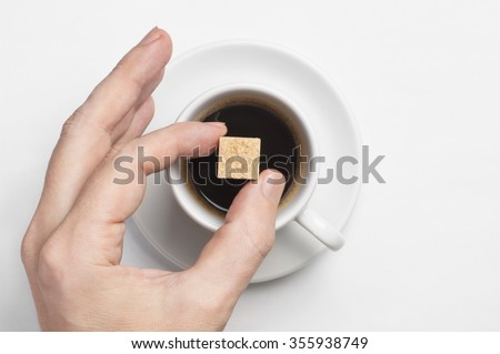 Male hand holding cane sugar cube over cup of black coffee against white background with space for text, top view, focus on sugar - stock photo