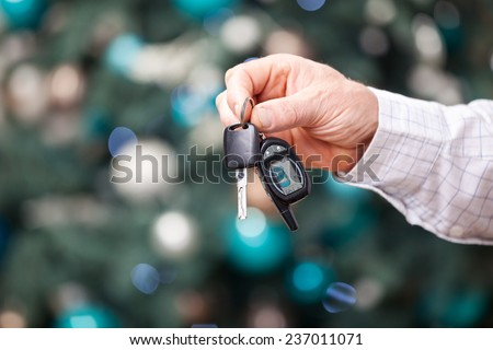 Male hand holding car key against Christmas background