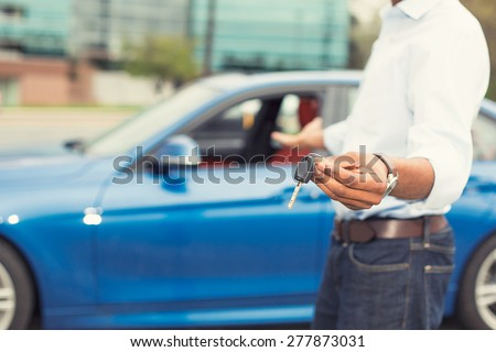 Male hand holding car keys offering new blue car on background - stock photo