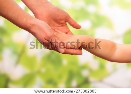 Male hand holding child, trust family concept - stock photo