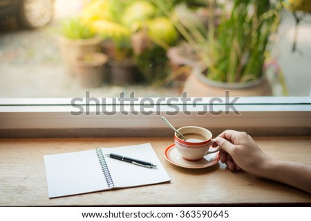 Male hand holding coffee cup on wood bar beside window at cafe in morning time