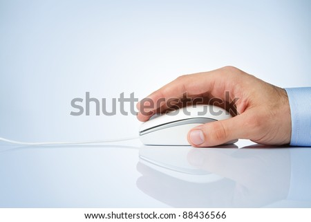 Male hand holding computer mouse with copy space - stock photo
