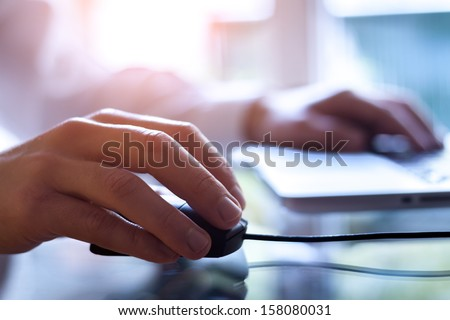 Male hand holding computer mouse with laptop keyboard in the background - stock photo
