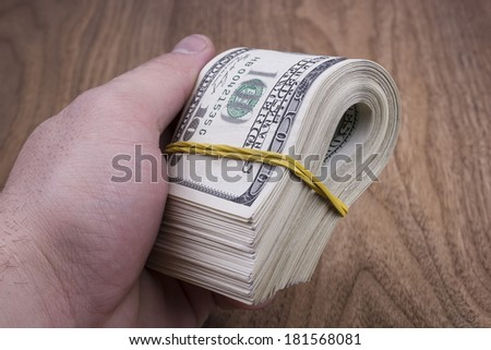 male hand holding dollars - stock photo